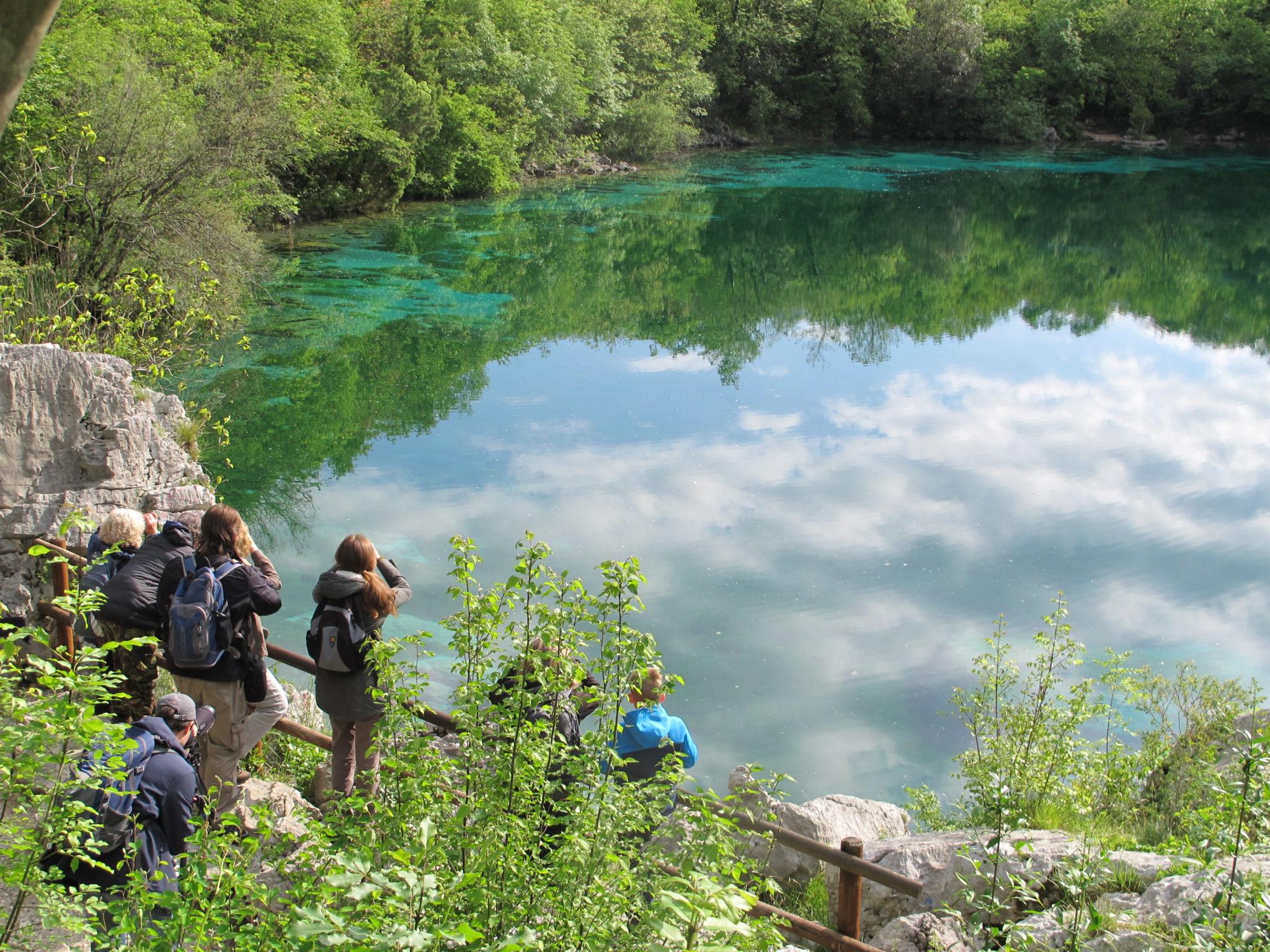 Lidé pozorující ptáky u jezera Cornino