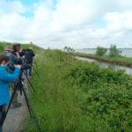 Lidé dívajíci de do stativových dalekohledů v deltě Pádu